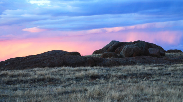 Sunset lit clouds over a rock formation near Laramie Wyoming.