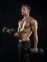 Mature Muscular bodybuilder holding dumbells weights with black background