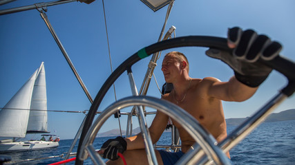 Young man skipper steering wheel during sea yacht race. Sailing, holidays and travel.