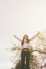 Mujer joven y feliz con sus brazos hacia el cielo y la luz del atardecer