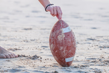 Close up of hand over from rugby ball on the beach. Hand of football player making touchdown. Sport concept and competition. Concept of summer vacation and leisure. Copy space.