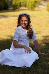 Obraz Śliczna dziewczynka w białej sukni siedzi na trawie. - fototapety do salonu