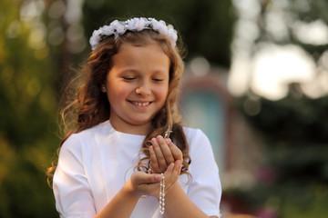 Fototapeta Radosna dziewczynka z różańcem w dłoniach. obraz