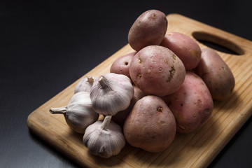 Pile of potatoes with garlic on wood board with black background