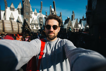 Funny bearded man backpacker smiling and taking selfie photo in London while travel