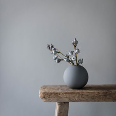 Vase on wooden table against gray wall
