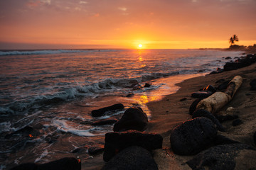 Waves from ocean crashing on rocks on beach at sunset in Hawaii