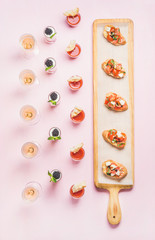Catering, banquet food concept. Various snacks, brushetta sandwiches, gazpacho shots, desserts with berries on corporate event, christmas, birthday, wedding celebration over pink background, top view
