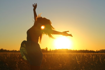 Attractive girl enjoy nature running, jumping, dancing in fields on sunset. Young woman in dress having fun outdoor. Summer holidays concept.