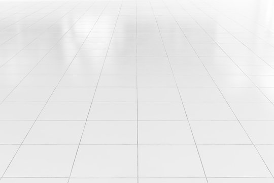 White tile floor background in perspective view. Clean, shiny, symmetry with grid line texture. For decoration in bathroom, kitchen and laundry room. And empty or copy space for product display also.