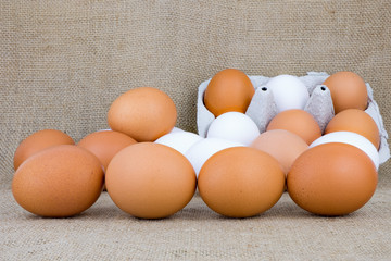 viele weiße und braune Hühnereier liegen auf einem Tisch