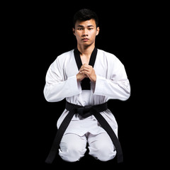 Portrait of a handsome asian man with taekwondo black belt . Iso