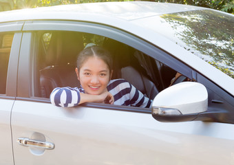 Beautiful asian girl smiling and  touching dashboard in car