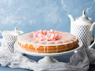 Bundt ring cake with sugar frosting decorated with pink flowers. Spring summer elegant breakfast set. Easter mother day festive treat. Selective focus