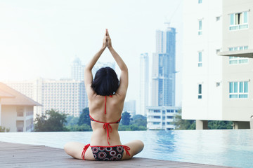 Woman in bikini relaxing with Yoga exercises