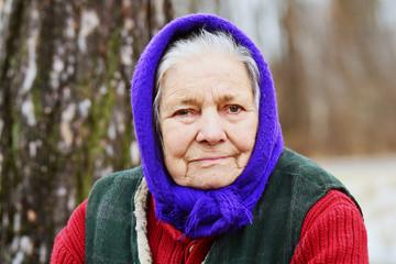 Portrait of old woman in blue headscarf