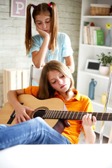 Teenagers learn to play guitar