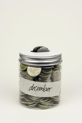Saving coins money by monthly in a jar on a white background