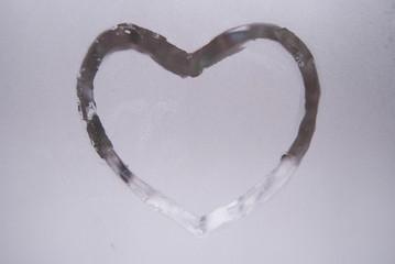 a heart drawn on a frozen window