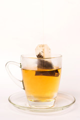 Tea bag dipped in the cup with hot water isolated on white background
