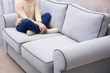 Young girl sitting on sofa in room