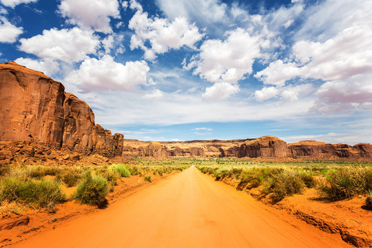 Sand road along red sandstones at Monument Valley