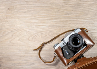 Old film camera in a brown leather case photographed on wood background.
