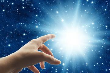 Wall Mural - woman hand touching a divine light in the universe like a spiritual mystical concept