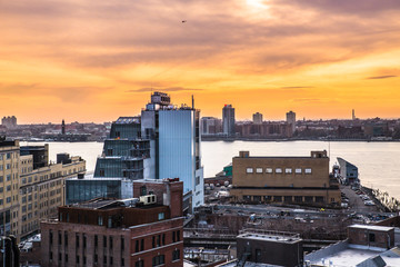 New York City sunset scene from the west side of Manhattan near the Meatpacking and Chelsea districts looking towards New Jersey with buildings and river in view.
