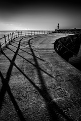 Mevagissey light house at dawn in black and white with long shadows. Cornwall UK