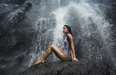 Beautiful slim model posing under waterfall wearing white swimwear