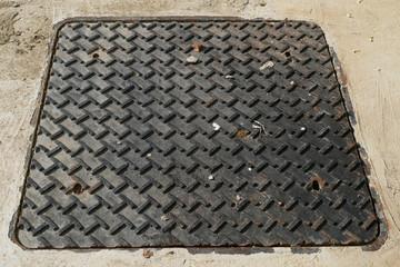 Black painted diamond steel plate on the sidewalk