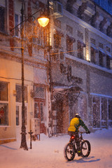 Winter story. Night snowfall on the street of the city.