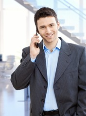 Young businessman with mobile phone at office