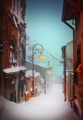 Winter story. Night snowfall in a silent street of the city.