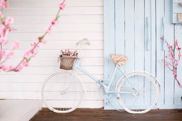White Bicycle With Beautiful Flower Basket on vintage background. Spring and easter