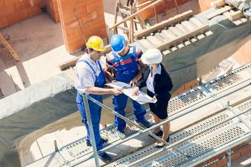 Arbeiter und Architektin besprechen Pläne auf Baustelle