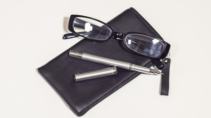 Leather black cover, bussines glasses and metal pen