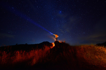 the man on mountian holding lighting on many star at night