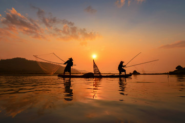 Silluate fisherman and boat in river on during sunrise,Thailand