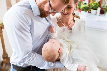 Junge Eltern mit ihrem Baby im Taufkleid in einer Kirche