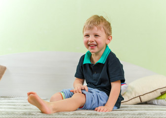 Skinny blond boy laughing heartily, sitting on a bed in the children's room, legs stretched out in front of him. Dressed in a casual black shirt and blue pants.
