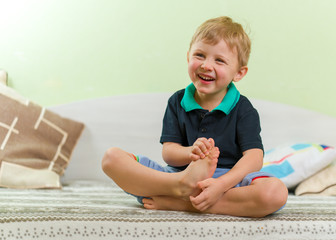 Skinny blond boy laughing heartily, sitting on a bed in the children's room, crossed legs and hands. Dressed in a casual black shirt and blue pants.