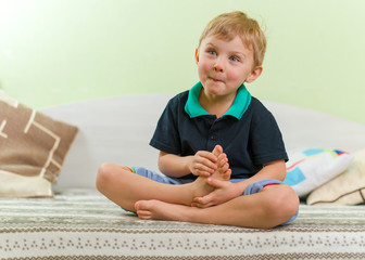 Skinny blond boy grimacing lips, sitting on a bed in the children's room, crossed legs and hands. Dressed in a casual black shirt and blue pants.