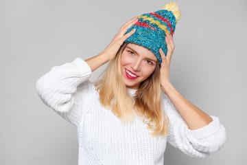 Happy smile girl fashion lifestyle portrait, wearing colorful hat, isolated on grey background