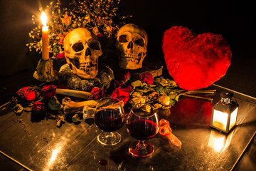 Two skulls, with bone and dry flowers in valentines night