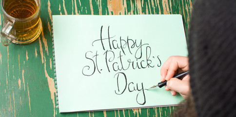 Man writing a Happy St Patrick day card