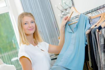 Lady in clothes shop, holding top