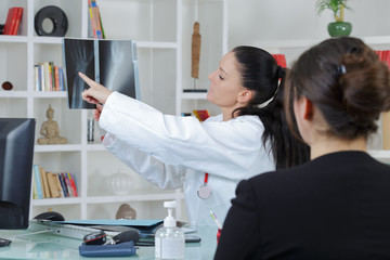 dentist and patient looking x-ray results in clinic