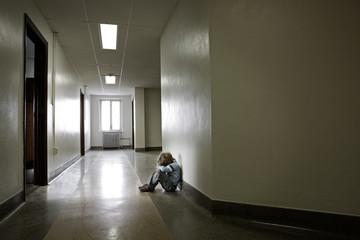 Depressed young boy sitting alone in a hallway